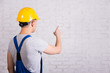 back view of man in blue builder uniform pointing at white wall