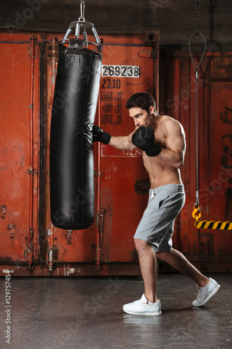 Photo Picture of handsome young boxer training in a gym