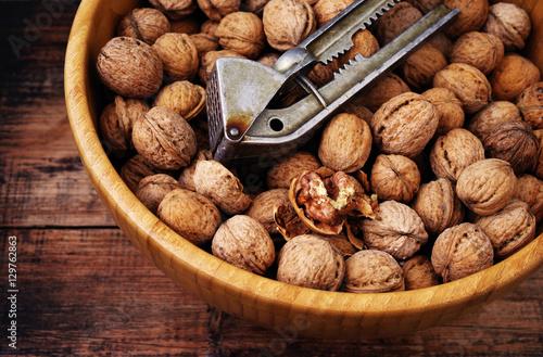 Keuken foto achterwand Baobab Walnuts in round wooden plate on old wooden surface. Walnuts