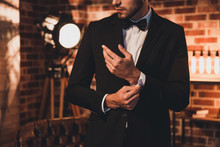Close Up Of Stylish Man In Black Suit Fastening Cufflinks In Lof