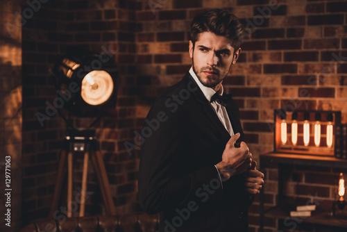 Fotografiet Brutal hansome businessman touching his black suit