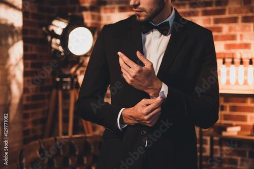 Fotografia Close up of stylish man in black suit fastening cufflinks in lof