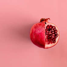 Red Pomegranate Fruit On Pastel Pink Background. Minimal Flat La