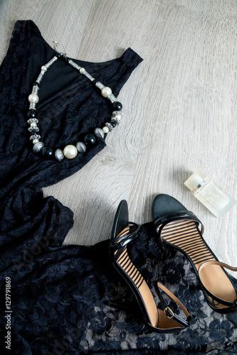 Plakat Strój dla kobiet. Czarna koronkowa sukienka, sandały buty, naszyjnik i perfumy na szarym tle drewnianych. Widok z góry, kopia przestrzeń.