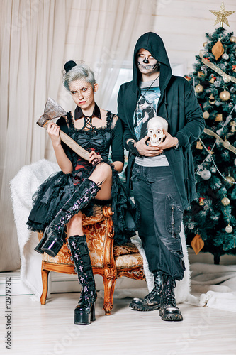 young gothic couple posing near a christmas tree goth style male model with skull and