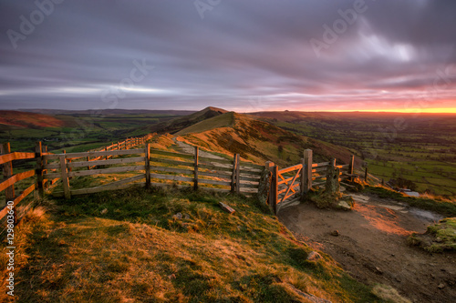 Keuken foto achterwand Lavendel Glowing red light from the rising sun shining on countryside gate at Mam Tor in the Peak District with moody clouds.