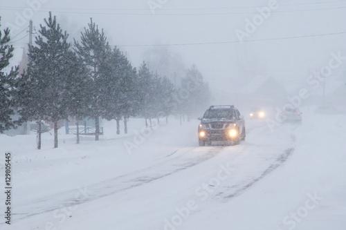 Zdjęcie XXL Zima, śnieg, zamieć, słaba widoczność na drodze. Samochód podczas zamieci na drodze z reflektorami.