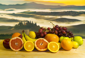Fototapeta Owoce fruits on a wooden table and Tuscan landscape at sunrise