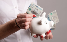 Woman Holding A Piggy Bank And New Five Pound Notes