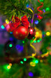 Christmas toys on Christmas tree with illumination. Bright vibrant baubles on blurred illuminated background and bokeh with soft focus. Merry Christmas and Happy New Year.