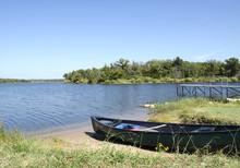 Green Canoe On The Lake Shore