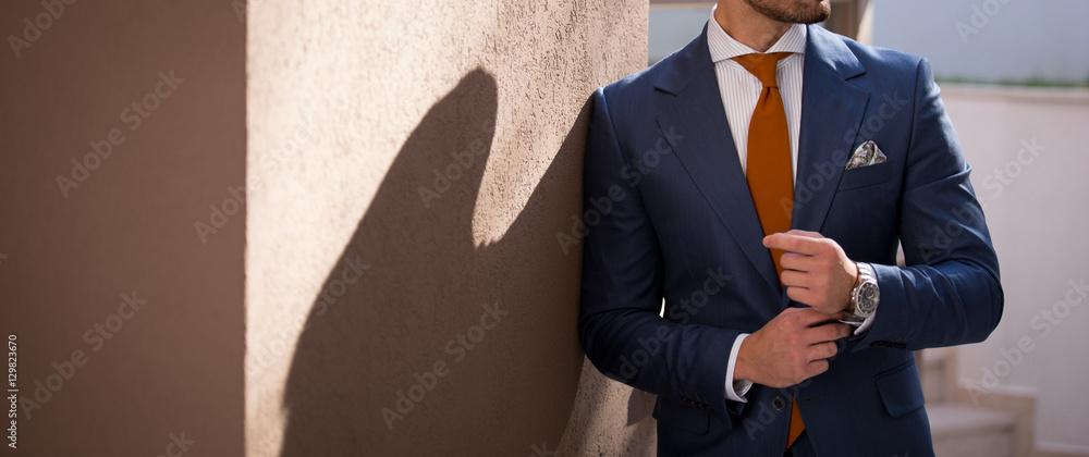 Fototapeta Male model in a suit posing outdoors