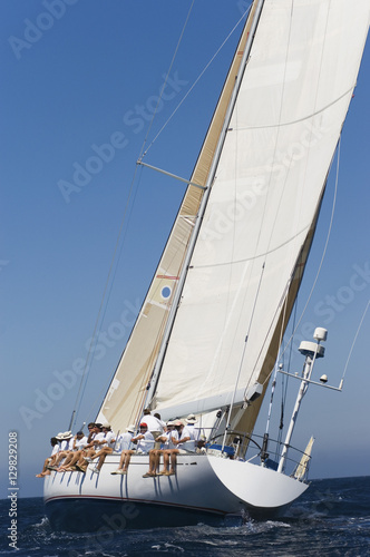 Poster Zeilen Group of crew members sitting on the side of a sailboat in the ocean