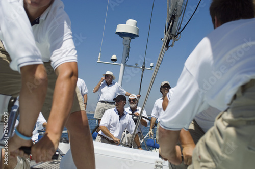 Fotografia Portrait of a smiling sailor with crew on the sailboat deck against clear sky