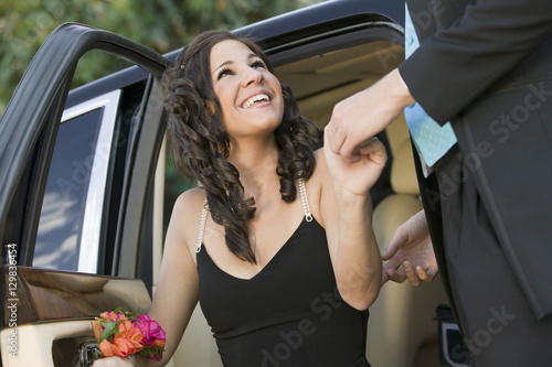 Fotografia Well-dressed teenager girl being helped out of limo by date