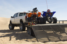 Quad Bikes On Trailer Behind Pickup Truck In Desert