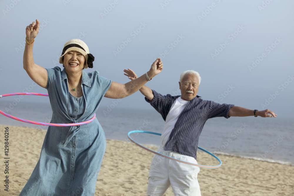 Fototapety, obrazy: Couple with hula hoops on beach
