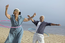 Couple With Hula Hoops On Beach
