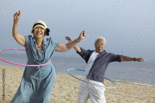 Stampa su Tela  Couple with hula hoops on beach