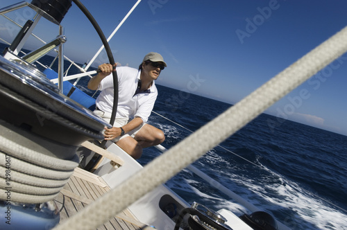 Cuadros en Lienzo Sailor at the helm of a yacht in the ocean against blue sky