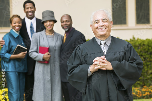 Photo Smiling Preacher in church garden worshipers in background portrait