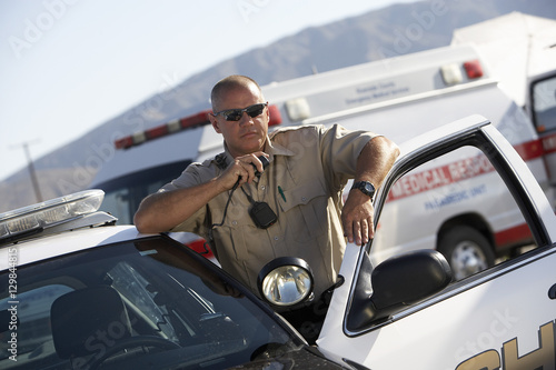 Canvas Police officer using two way radio by police car with ambulance in background