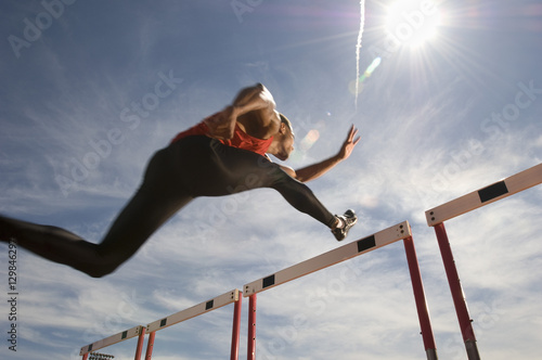 Low angle view of a male athlete jumping hurdle against the sky Canvas Print