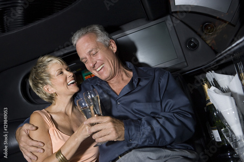 Photographie  Happy mature couple toasting champagne sitting in limousine and toasting