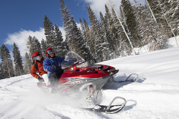 Fototapeta Couple driving snowmobile on snow covered track