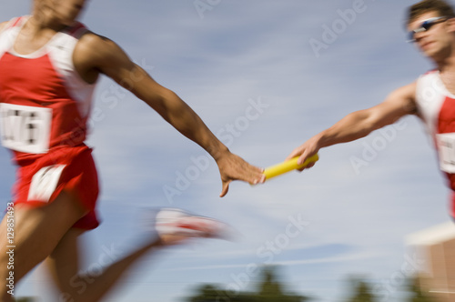 Fotografia  Blurred motion male runners passing baton in relay race