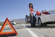 Full length of a young woman refueling her car with warning triangle on the foreground