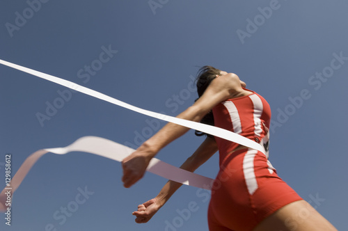 Low angle view of young female athlete crossing finish line against clear blue s Wallpaper Mural