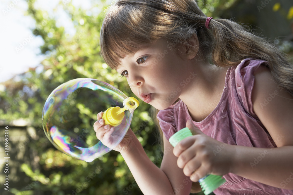 Fototapety, obrazy: Closeup of a little girl blowing soap bubbles in the backyard