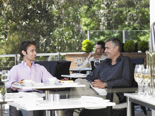 Photo  Happy businessmen conversing at outdoor cafe