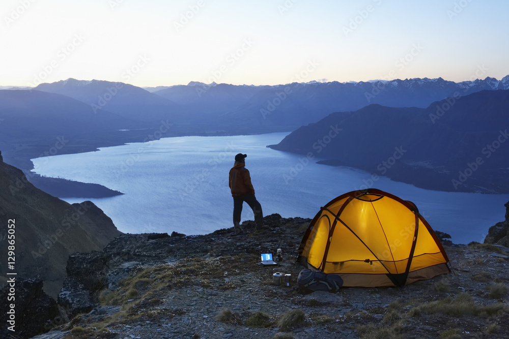 Man looking at lake by illuminated tent at dusk