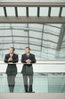 Two businessmen looking away while standing against glass railing in office