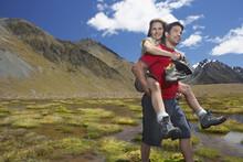 Man Giving Woman Piggyback Ride Through Pond Near Mountains