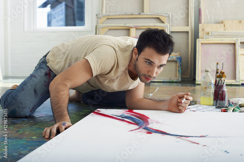 Young male artist looking at canvas on studio floor Wallpaper Mural
