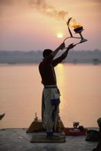 Hindu Man Worshipping In Front Of Setting Sun, River Ganges (Ganga), Varanasi (Benares), Uttar Pradesh State