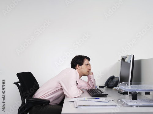 side view of a bored male office worker looking at notes on computer