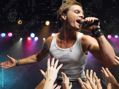 Obraz Young man singing on stage in concert with adoring fans reaching towards him - fototapety do salonu