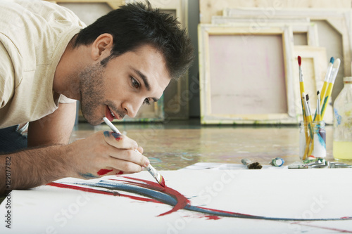Closeup of a young man painting on canvas on studio floor Tablou Canvas