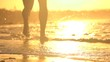 CLOSE UP DOF: Young man jogging in shallow ocean water at stunning orange sunset