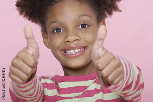 Closeup portrait of a happy girl giving double thumbs up on pink background Wallpaper Mural