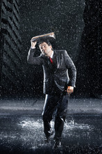 Full Length Of A Young Businessman Covering Head With Binder While Running Through Rain