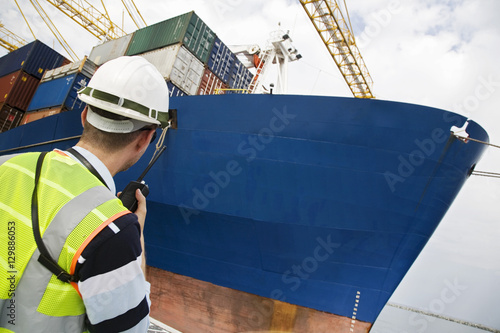 Rear view of a man in hard hat using walkie talkie at container terminal