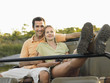 Young couple sitting in jeep with woman holding binoculars