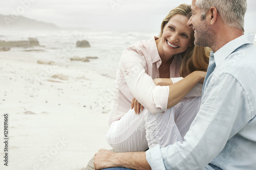 Fotografia  Happy loving couple sitting on beach