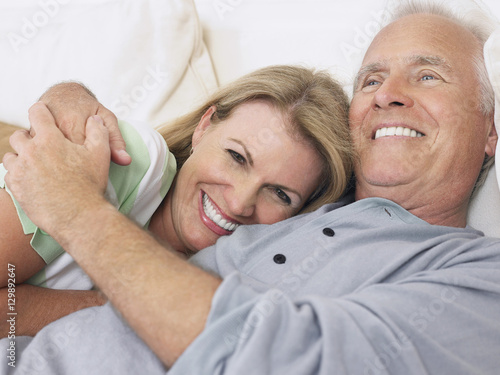 Canvas Print Closeup of a happy middle aged couple embracing in bed