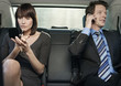 Young businesswoman applying lip gloss and businessman using cell phone in car
